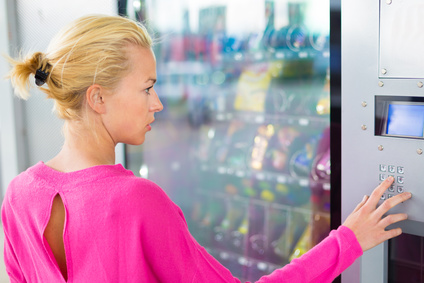 Caucasian woman wearing pink top using a coin operated modern vending machine. Her hand is placed on the dial pad and she is looking on the small display screen.